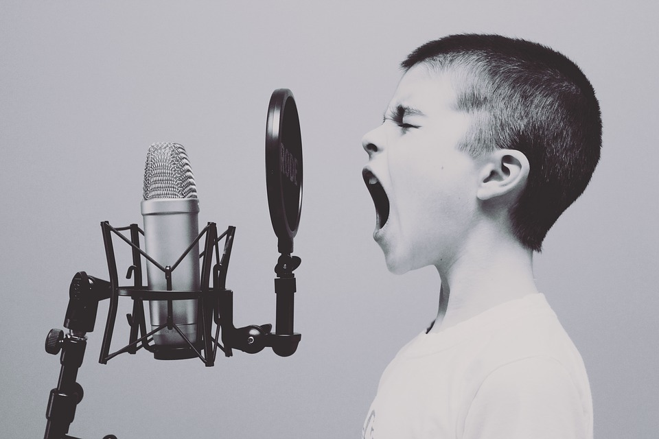 Boy belting out while recording