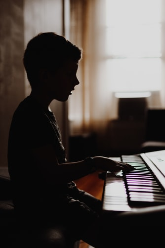 a kid playing a piano