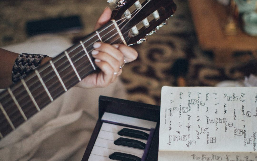 person's hands playing guitar in front of a keyboard and open notebook